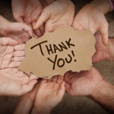 Thank You written on cardboard being held in hands by a group of people.  Stock image of a lot of hands holding torn cardboard.